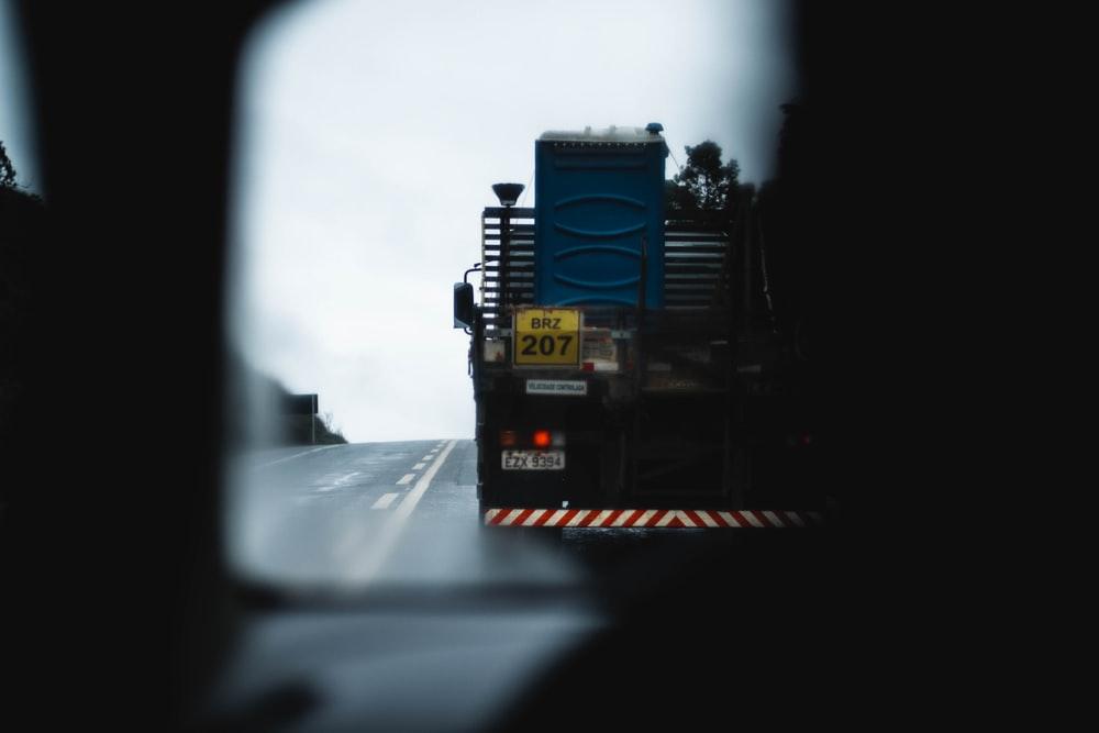 blue and black truck on road during daytime