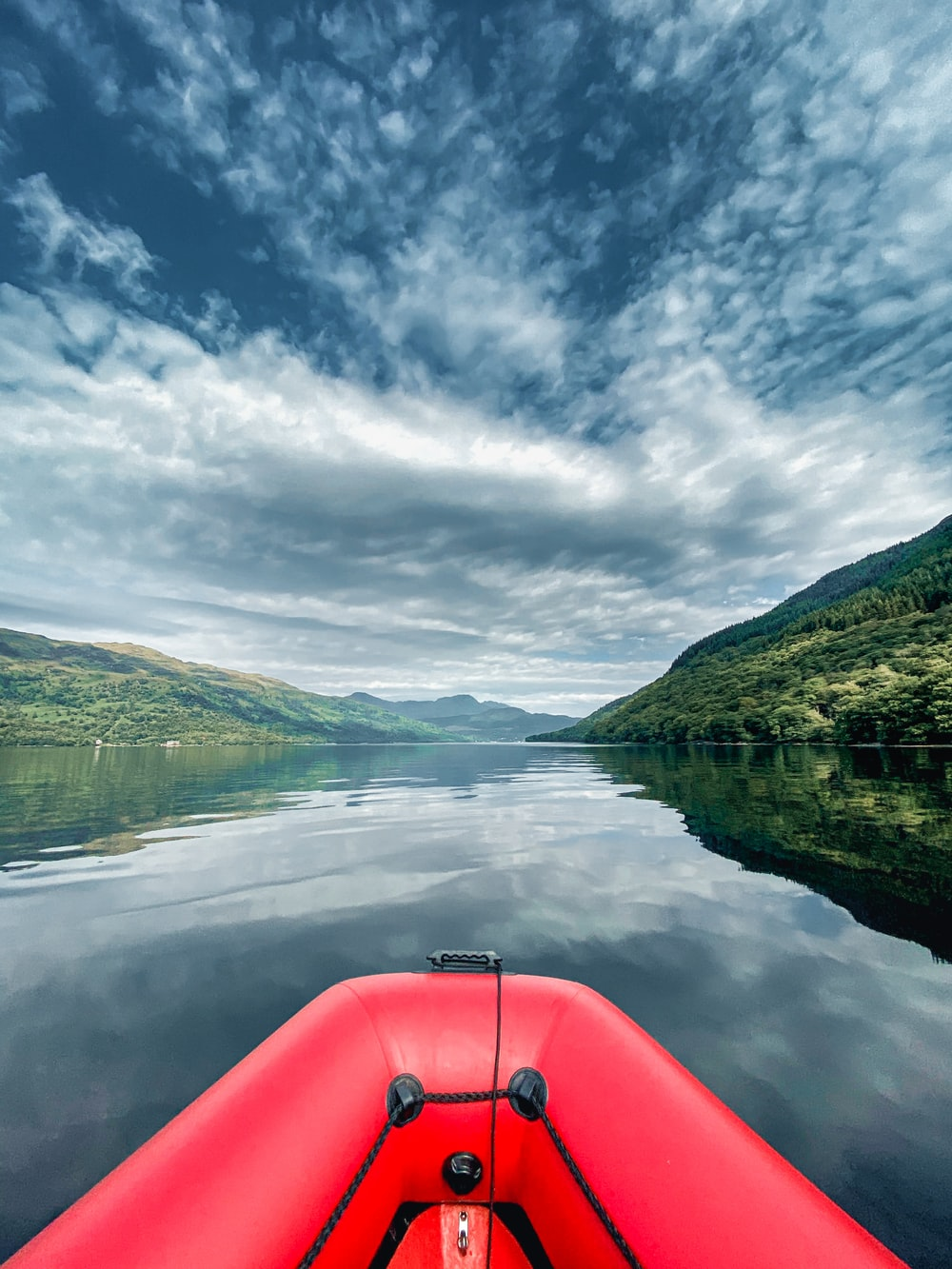 red kayak on lake near green mountains under white clouds and blue sky during daytime