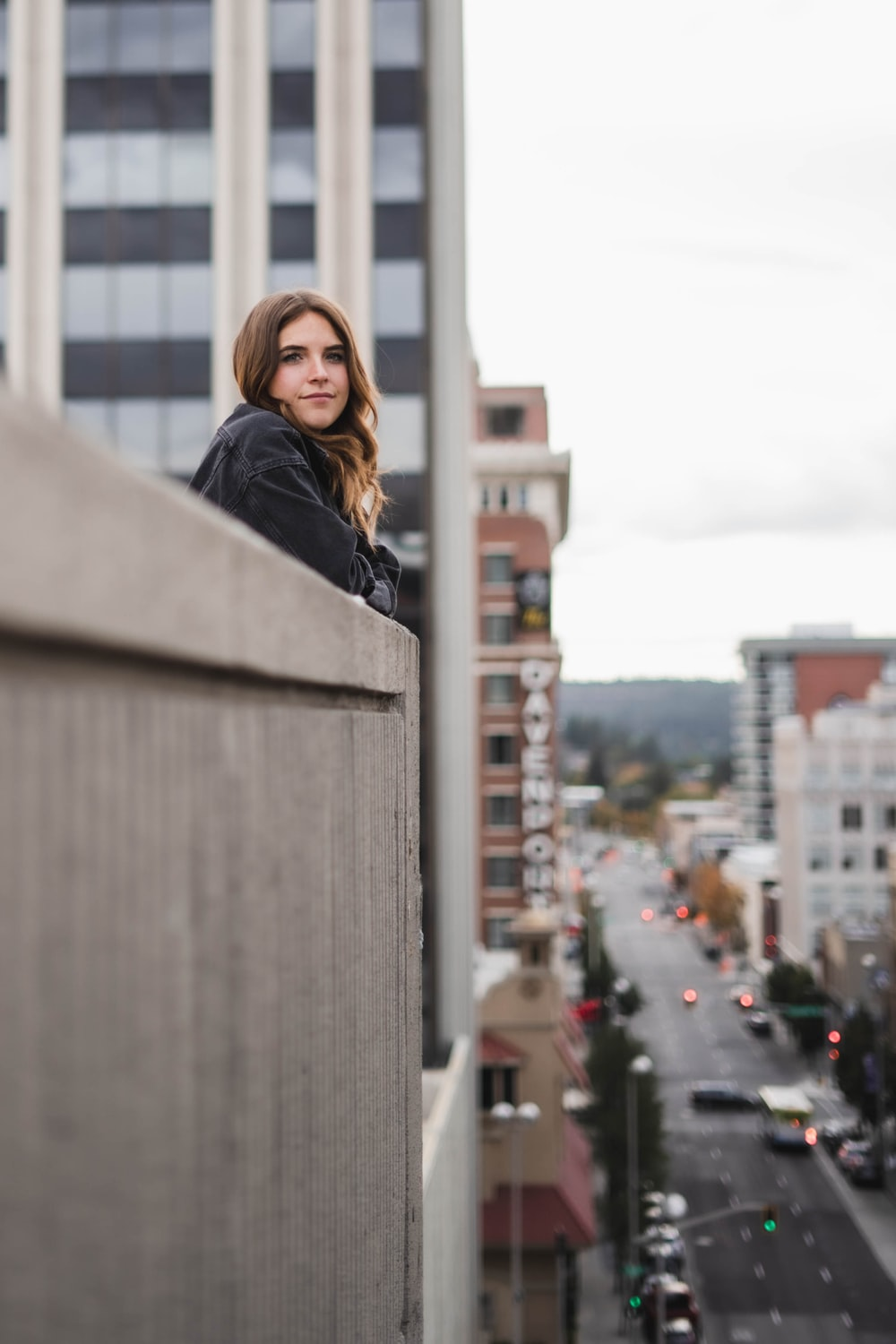 woman in black leather jacket standing near building during daytime