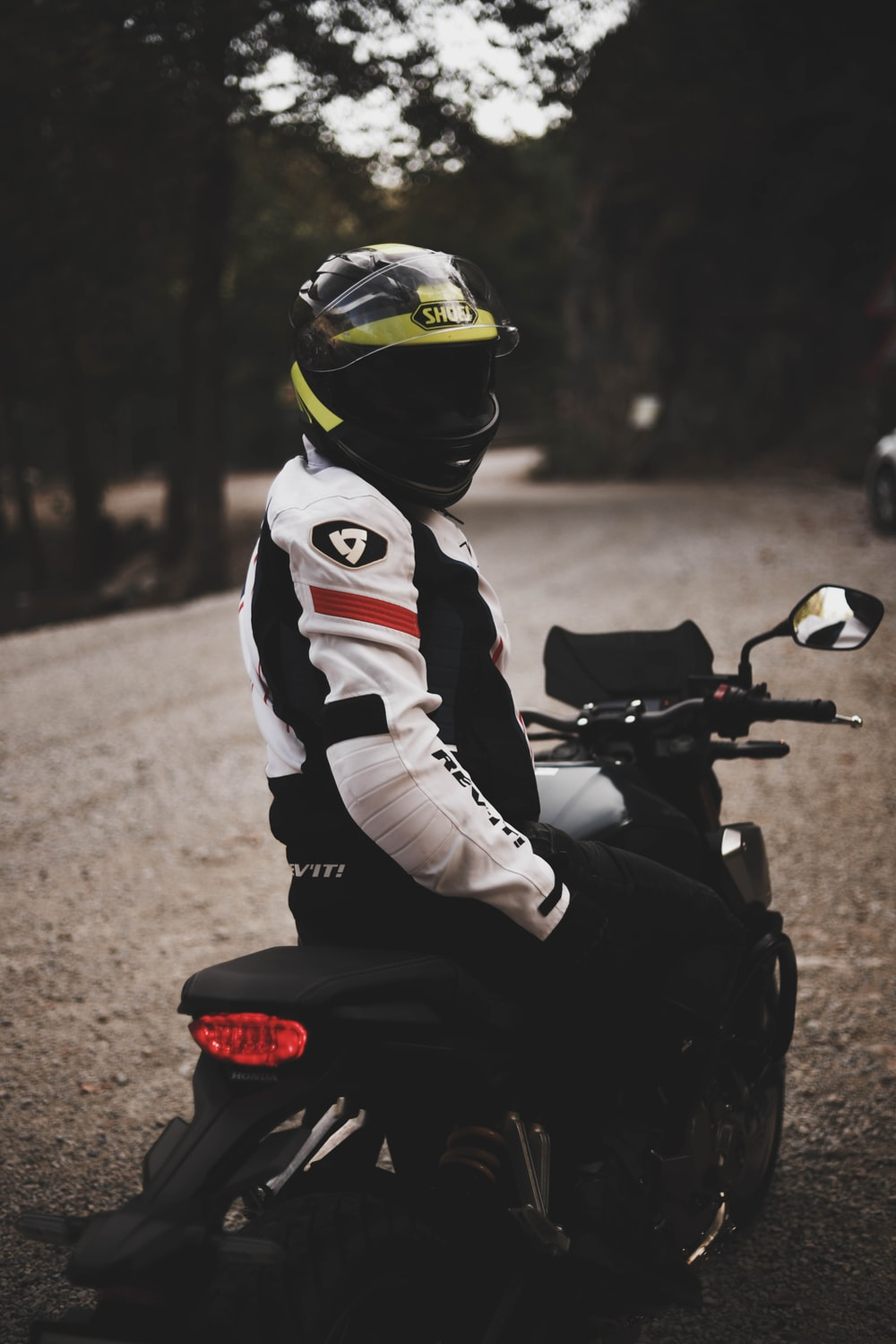 person in white red and black motorcycle helmet riding on black motorcycle during daytime