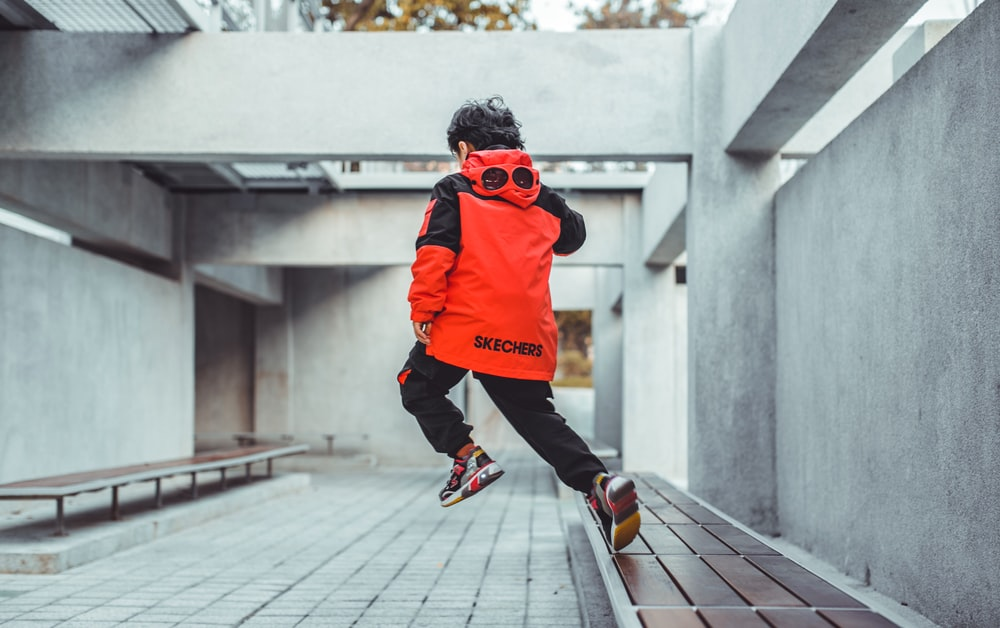 man in orange hoodie and black pants running on gray concrete pavement during daytime