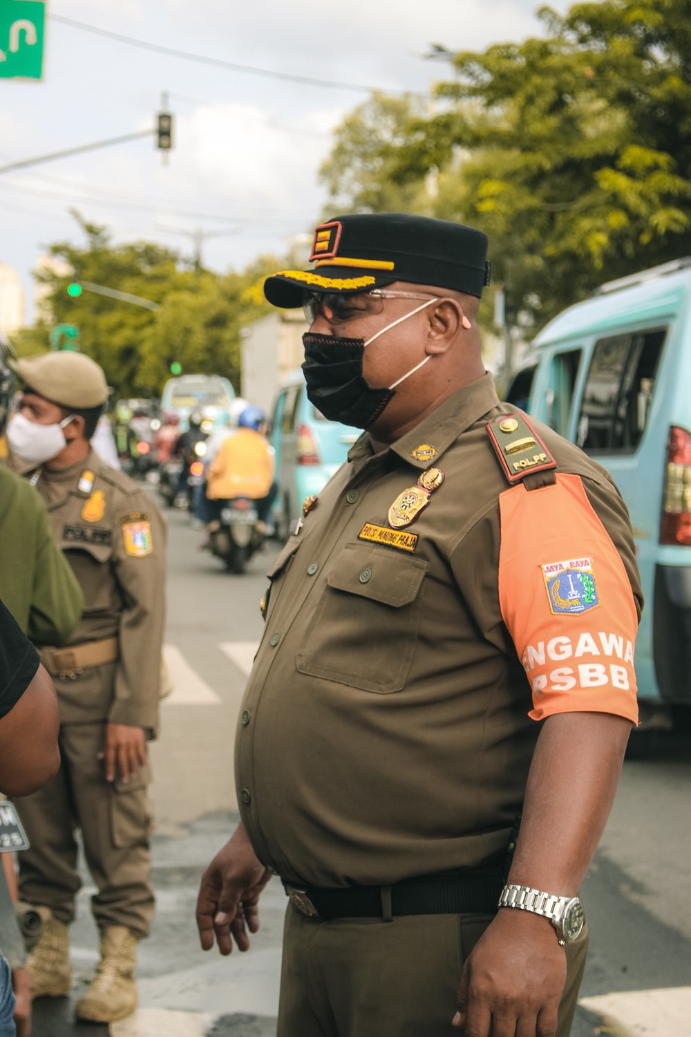 man in green uniform standing near people during daytime