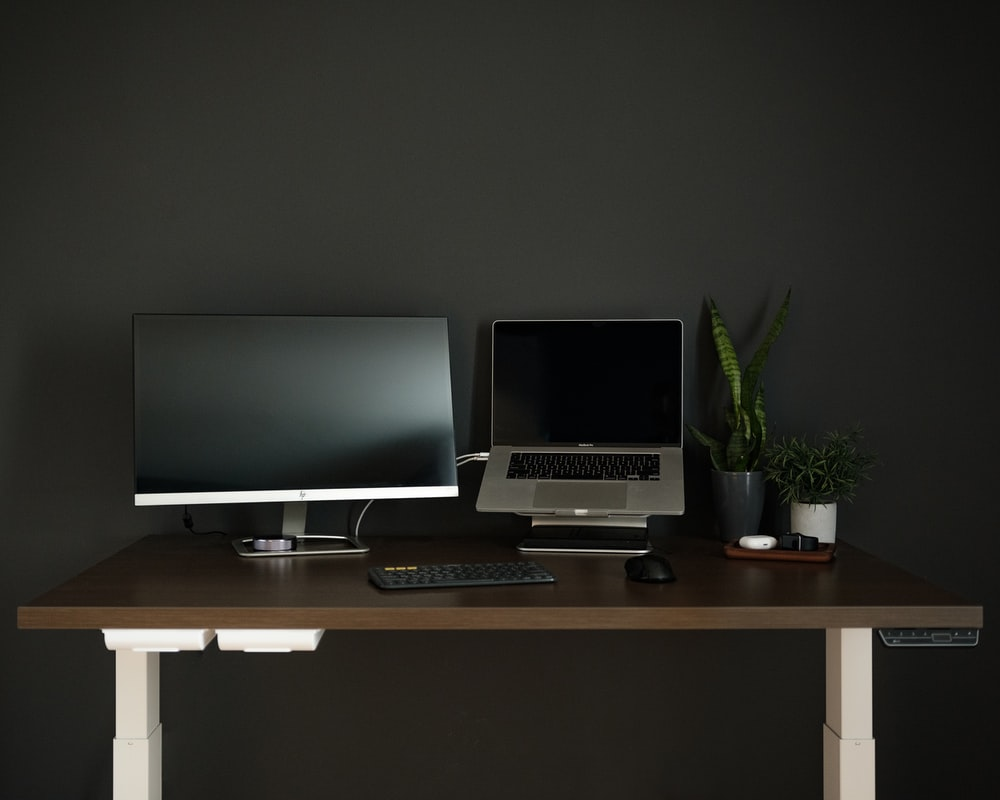 silver flat screen computer monitor on brown wooden desk