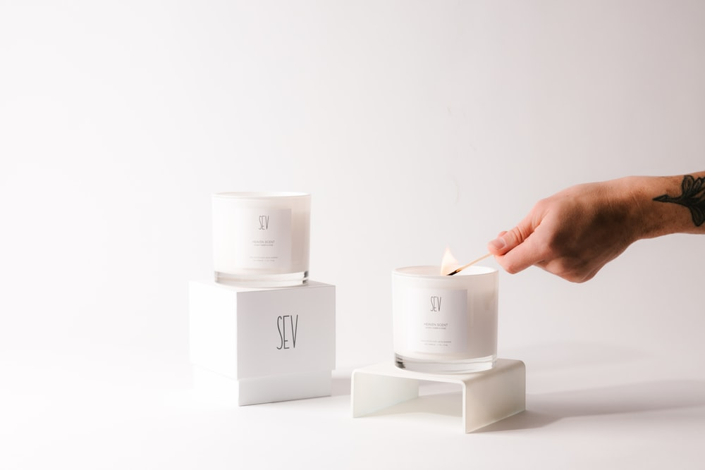 person holding white candle holder