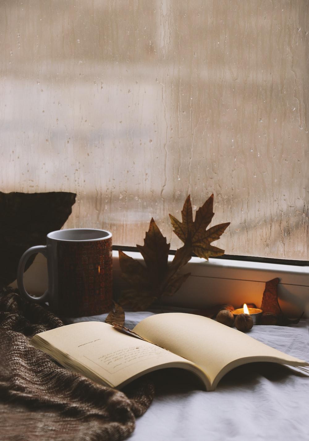 opened book beside white ceramic mug on table