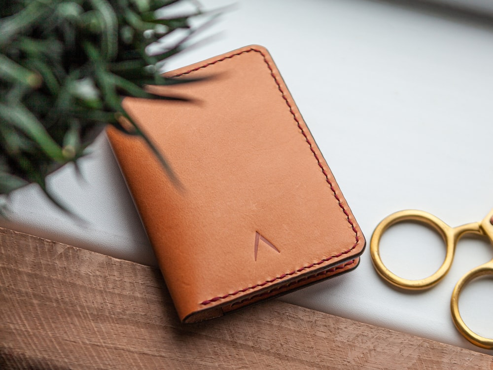 brown leather bifold wallet beside gold ring