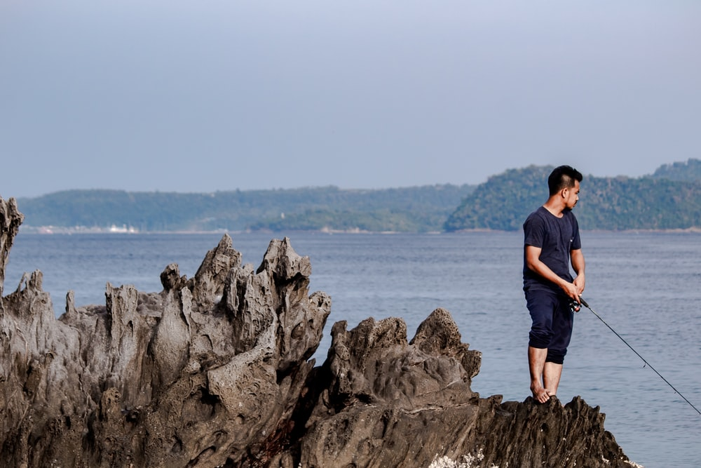 man in black t-shirt standing on rock formation near body of water during daytime