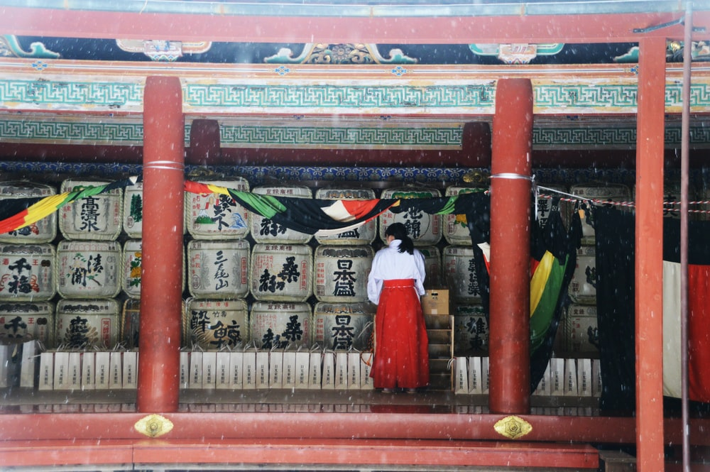 woman in white dress standing on red wooden door