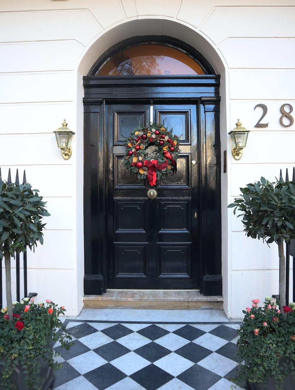 black wooden door with red flowers