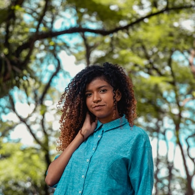 woman in blue button up shirt standing near brown tree during daytime