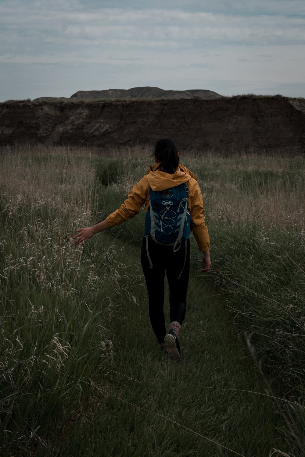 woman in yellow jacket and black pants walking on green grass field during daytime