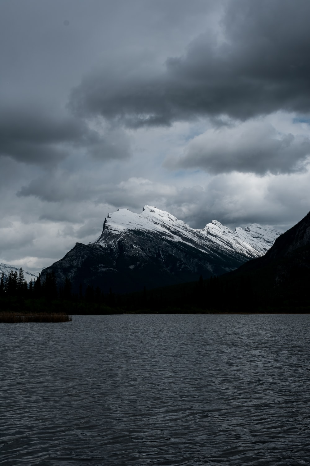 snow covered mountain near body of water under cloudy sky during daytime