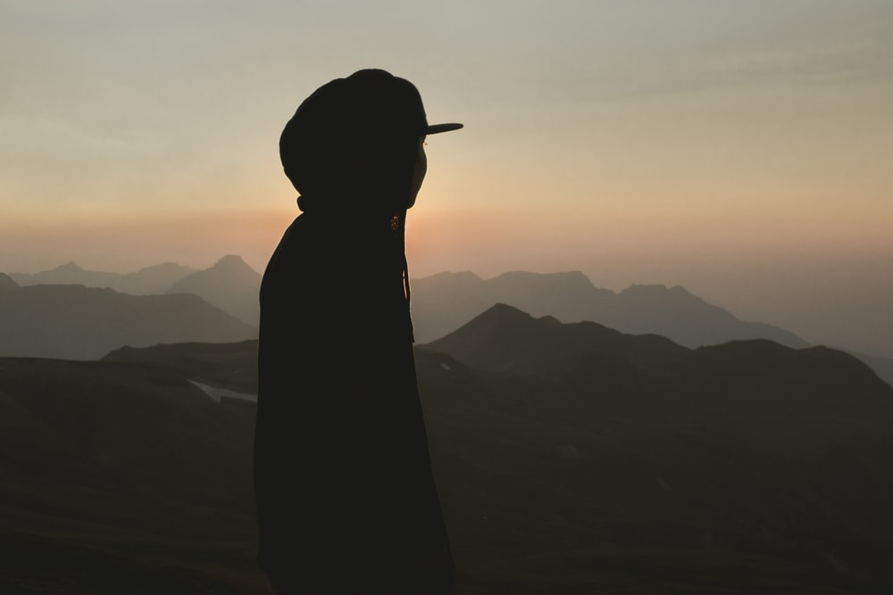 silhouette of woman standing on mountain during sunset