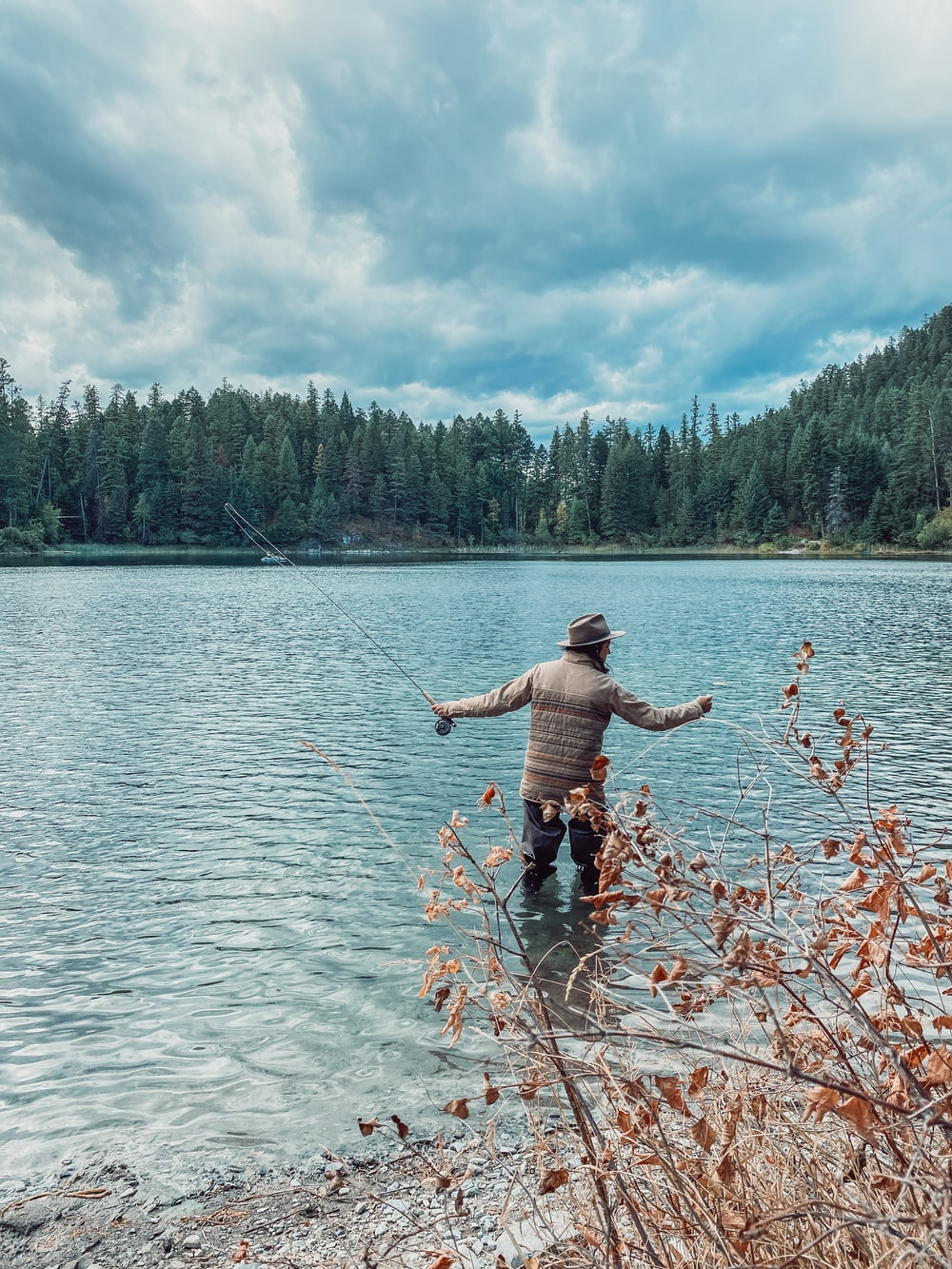 man in black shorts standing on body of water during daytime