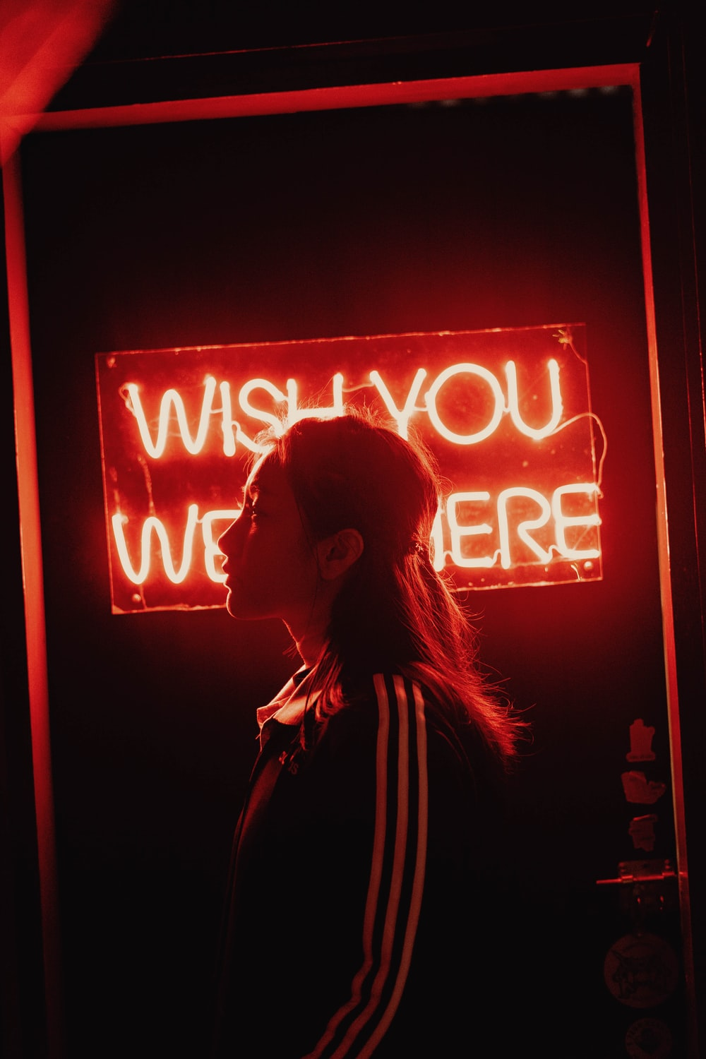 woman in white jacket standing in front of red and white neon signage