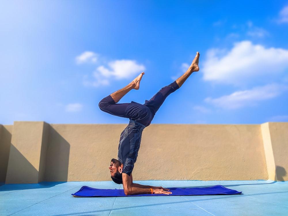 man in black pants and black shirt standing on blue yoga mat