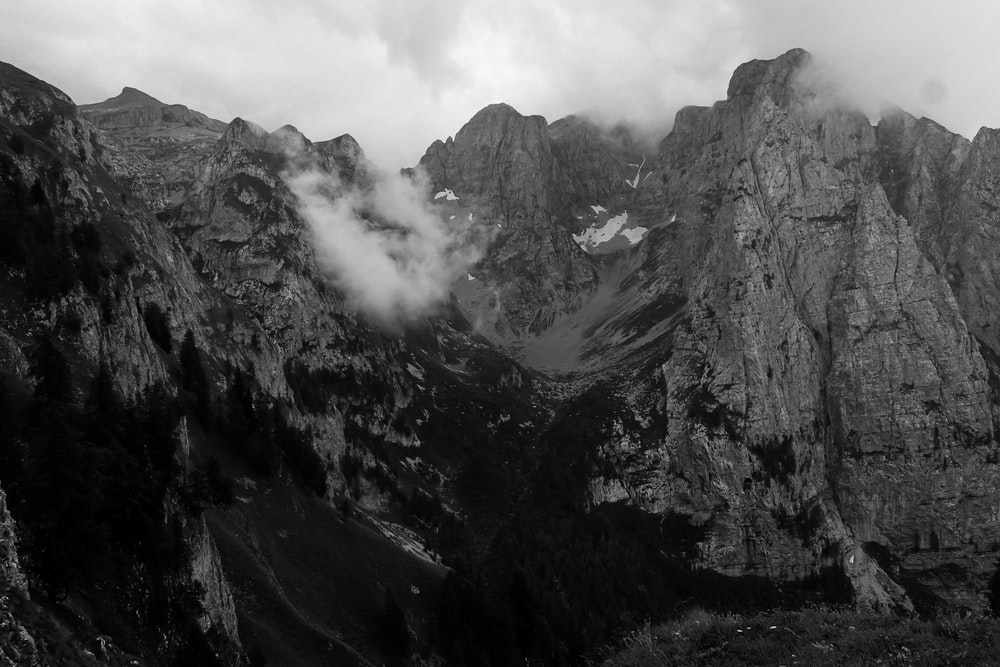 grayscale photo of mountains and clouds