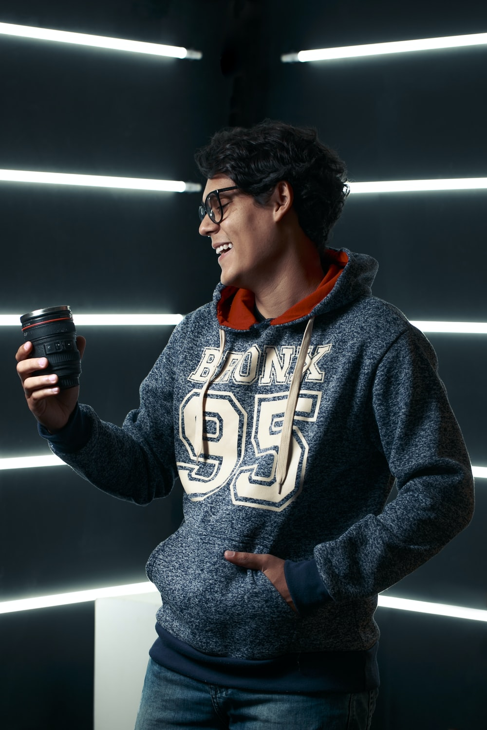 man in gray hoodie holding black disposable cup