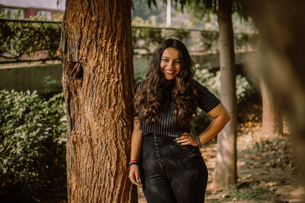 woman in black shirt and blue denim jeans standing beside brown tree