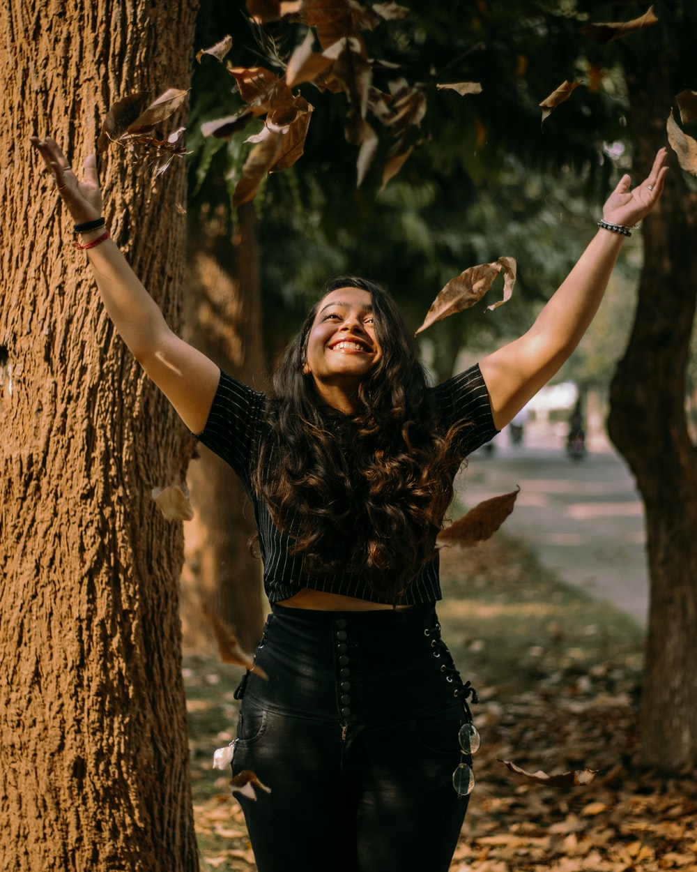 woman in black long sleeve shirt and black denim jeans standing beside brown tree trunk during