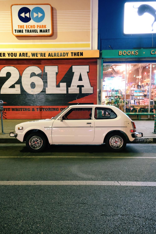 white sedan parked beside store