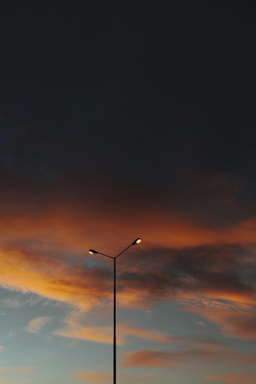 black street light under orange and blue sky