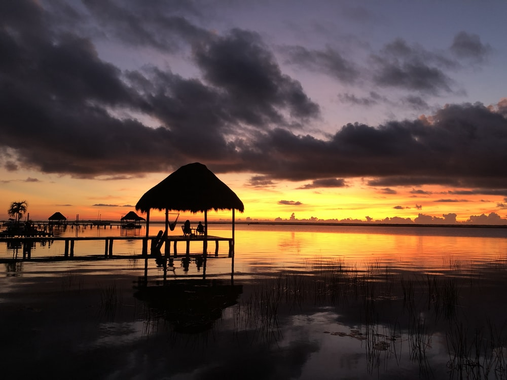 brown wooden beach house on body of water during sunset