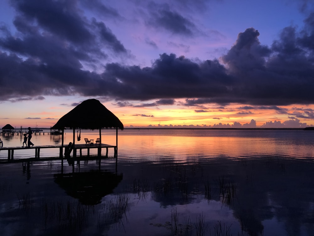 silhouette of gazebo on water during sunset