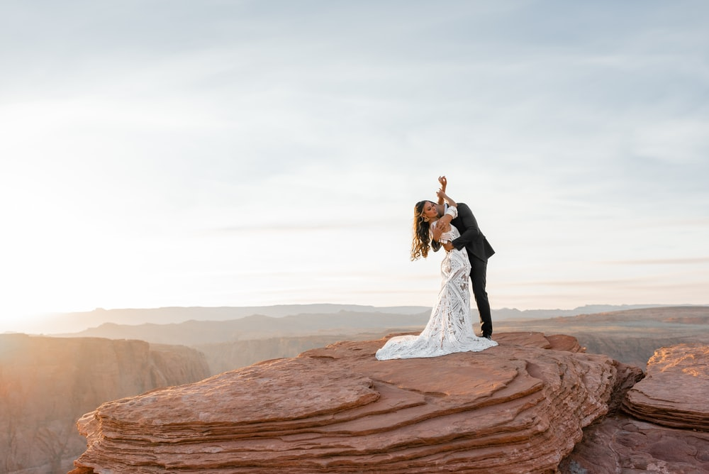 man and woman kissing on brown rock formation during daytime