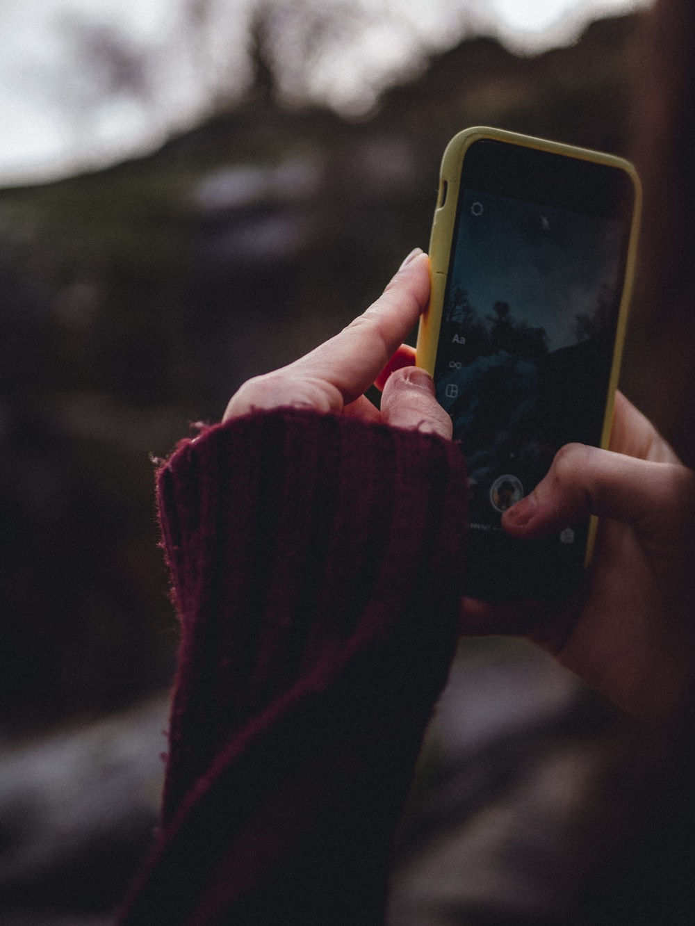 person holding yellow iphone 5 c
