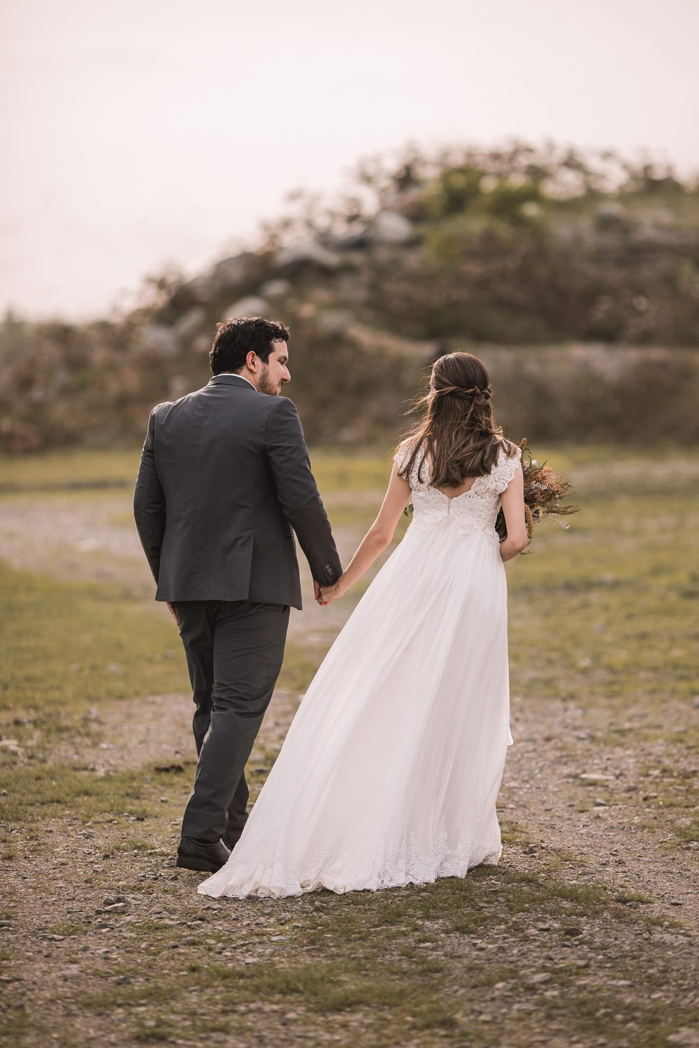 man in black suit and woman in white wedding dress kissing on green grass field during