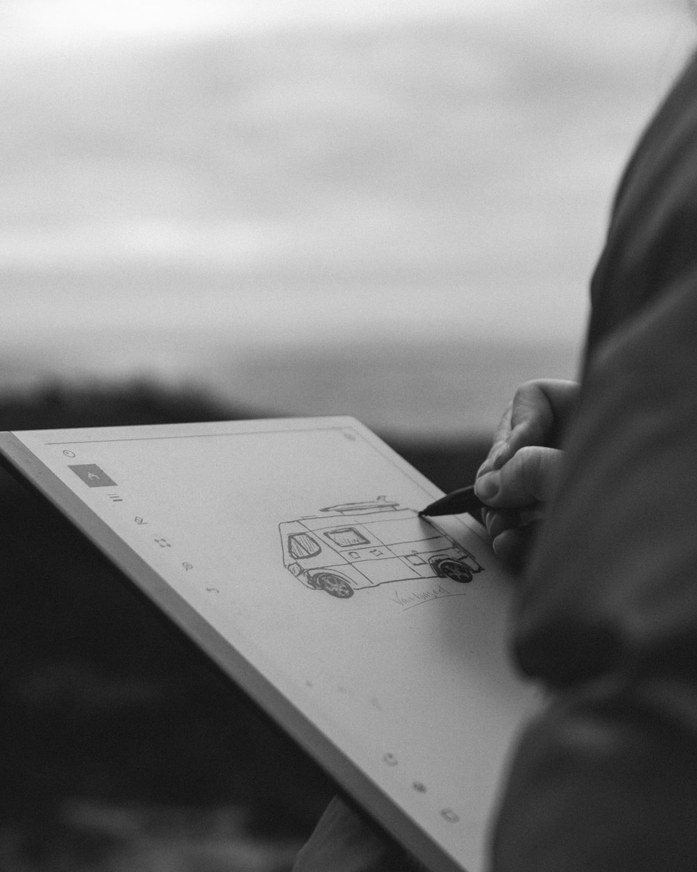 grayscale photo of person holding pen writing on white paper