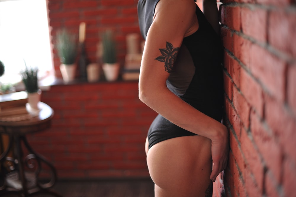 woman in black tank top and white panty leaning on red brick wall