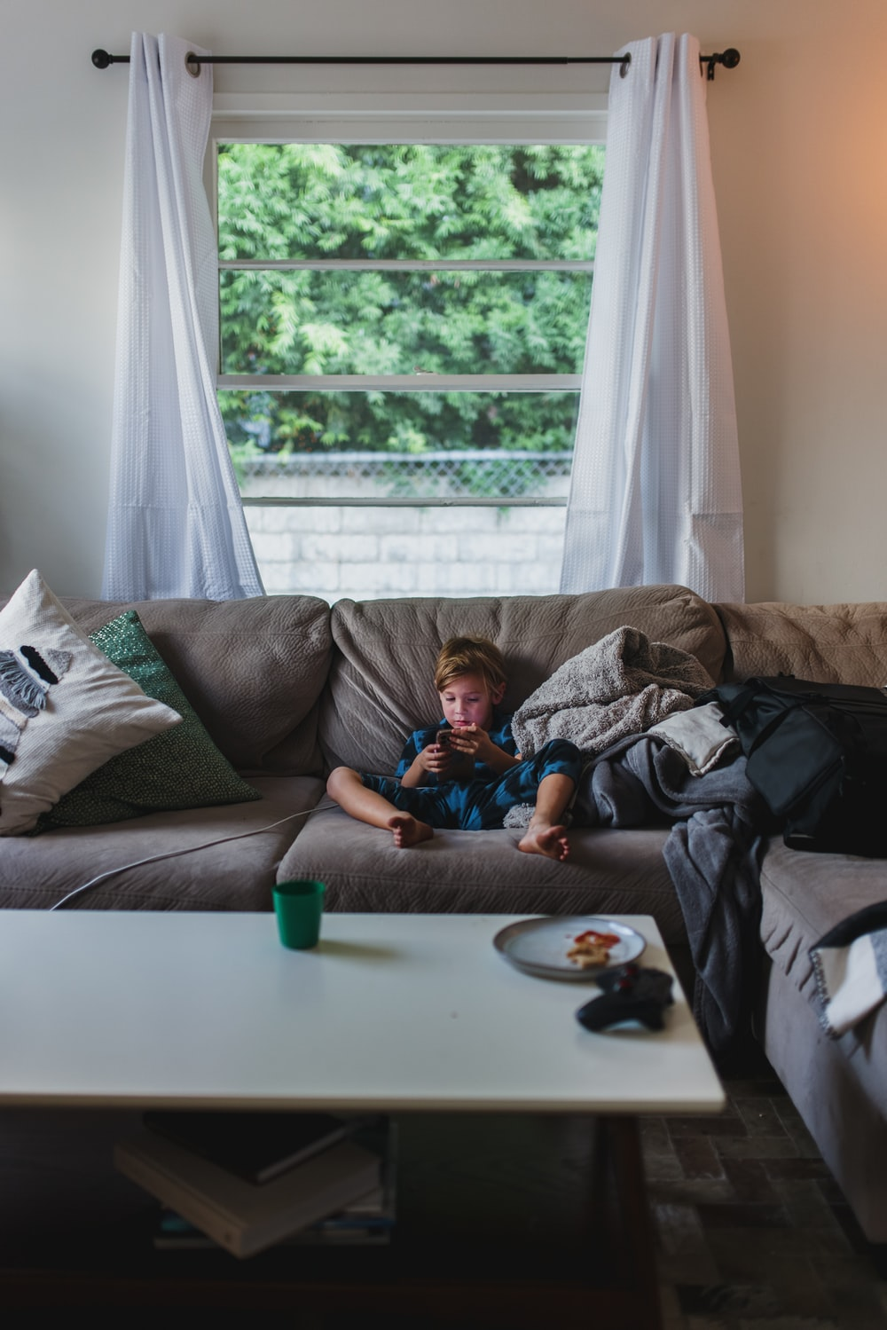 boy in blue shirt lying on gray couch