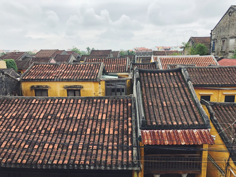 brown and black concrete houses under white clouds during daytime