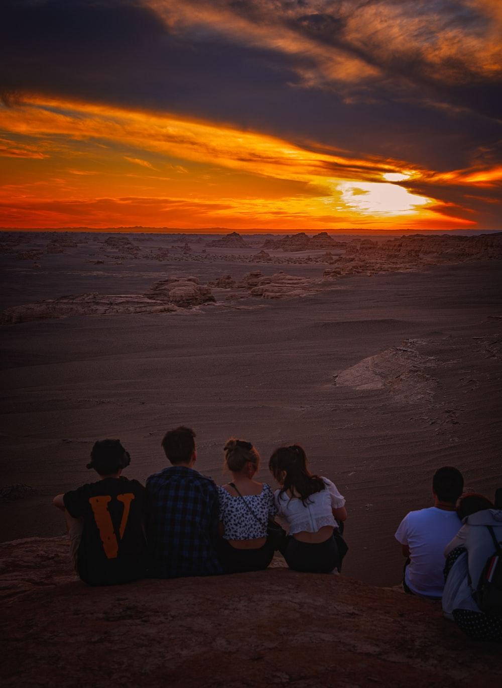 3 men sitting on seashore during sunset