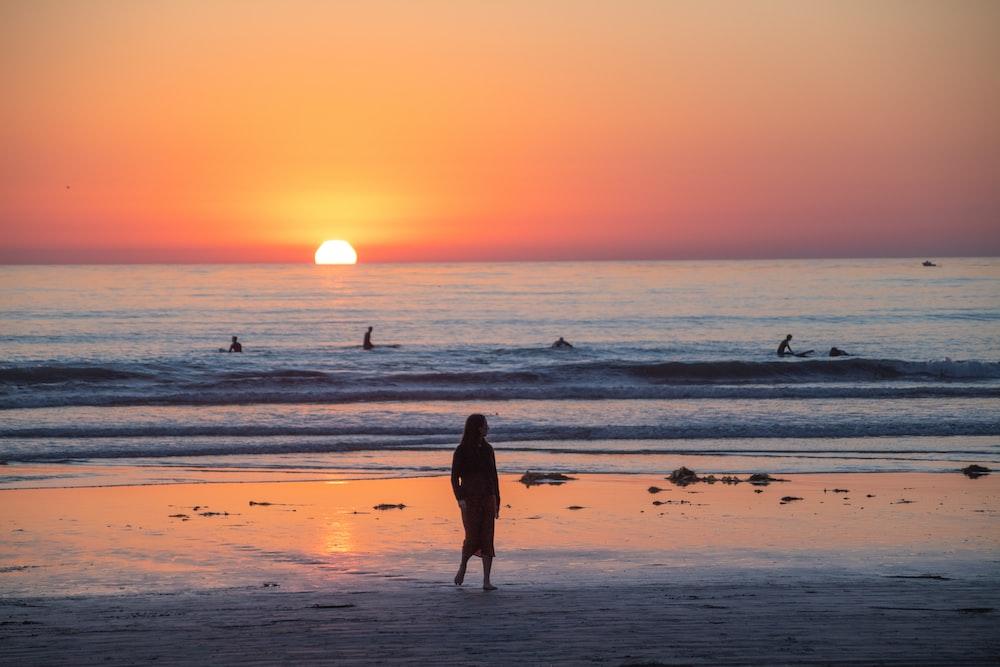 woman in black dress walking on beach during sunset