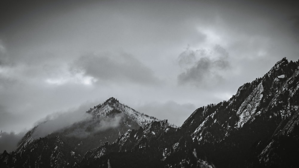 black and white mountain under white clouds
