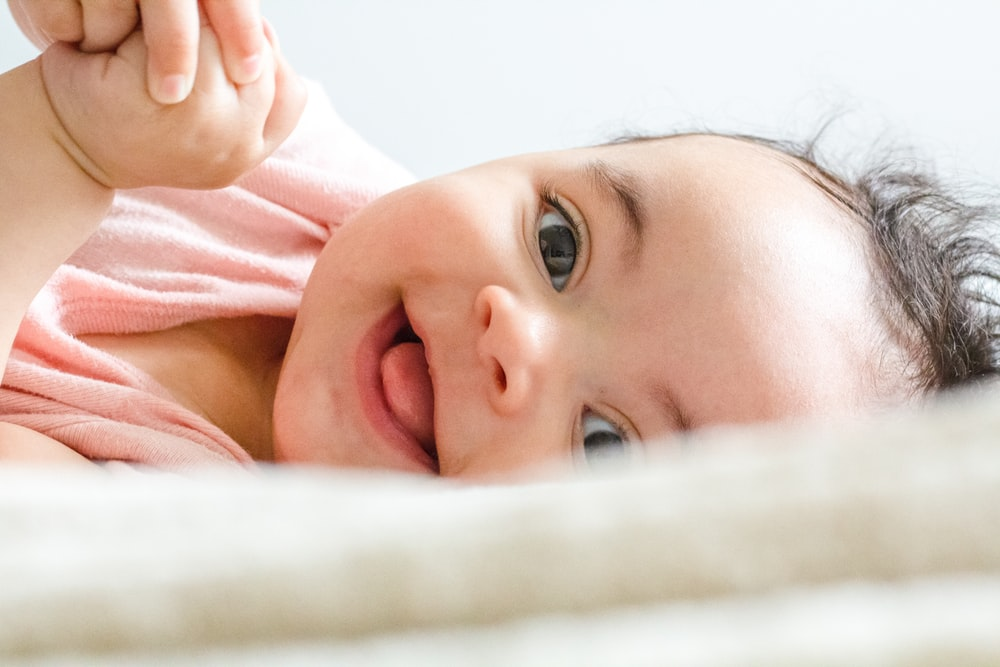 baby in pink shirt lying on white textile