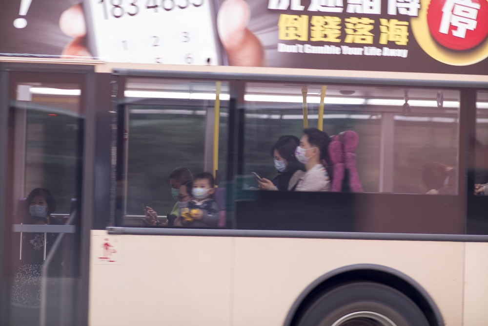 white and yellow bus with people inside