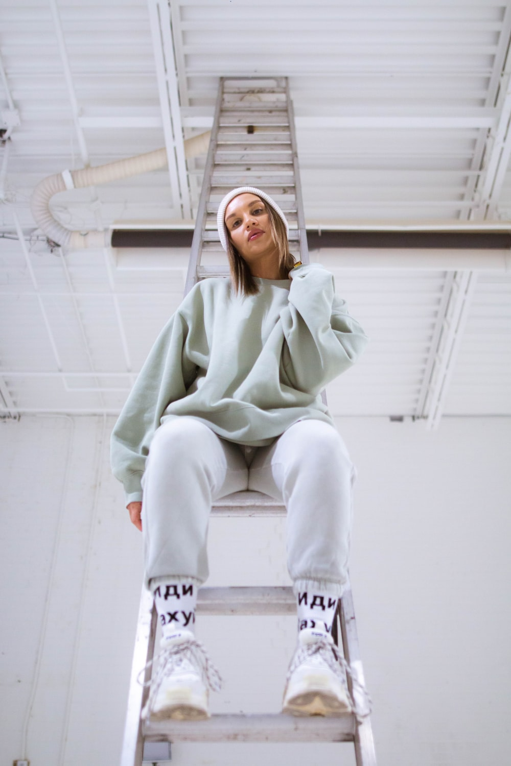 woman in green hoodie and white pants sitting on white concrete wall