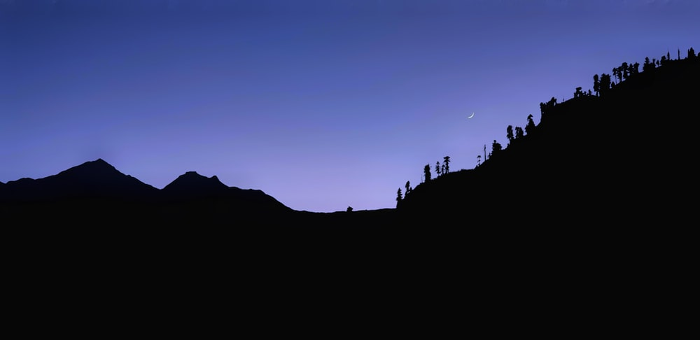 silhouette of people on mountain during sunset