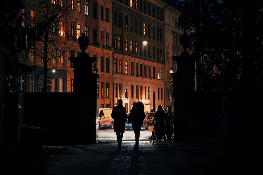 silhouette of people walking on street during night time