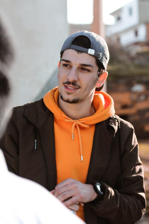 man in black and orange zip up jacket smiling