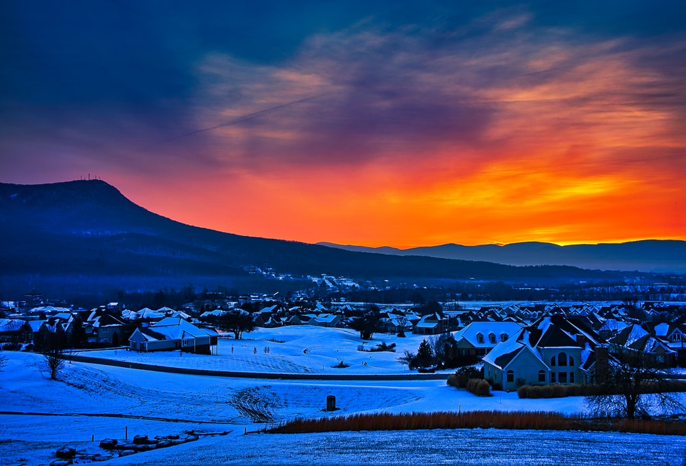 houses on snow covered ground during sunset