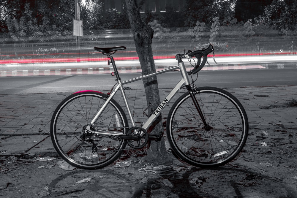 red and black road bike parked beside road