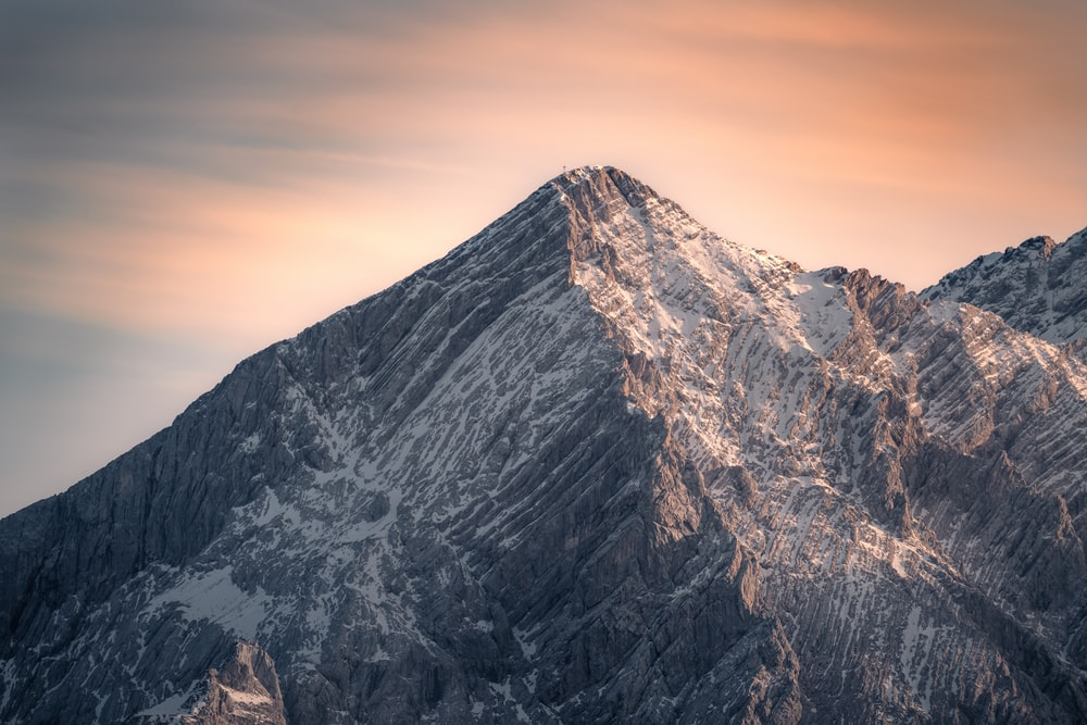 brown and gray mountain under orange sky