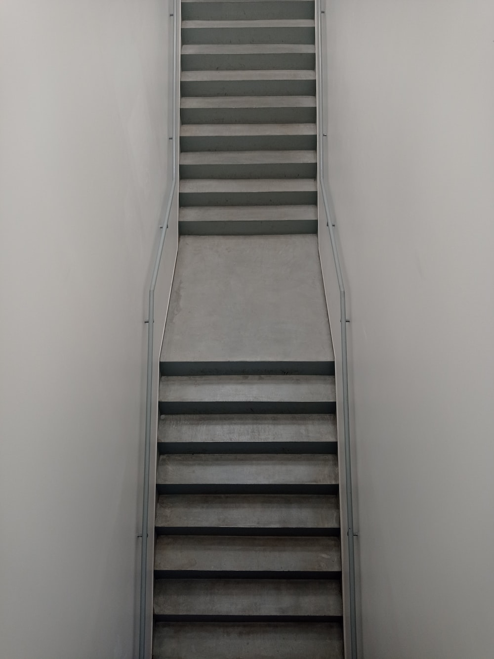 brown wooden staircase beside white wall
