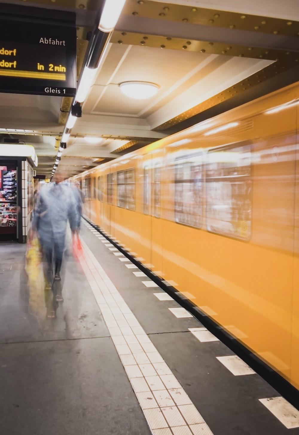 man in gray jacket walking on train station
