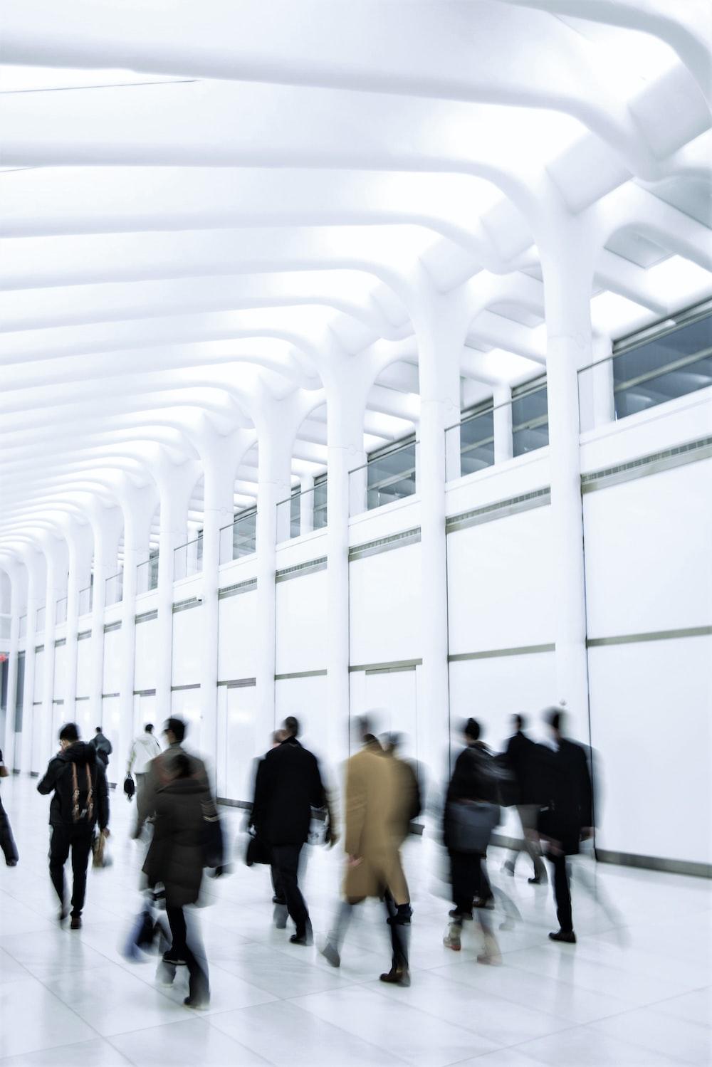 people walking on white hallway